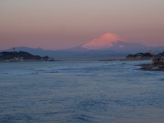 2018/2/14 ライトアップの夜明けて、いつもどおりの江の島灯台、富士の手前、僅かな霞が色づく下でサーファー達が右に左に