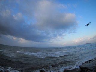 2018/4/12 雲がまだ重そうな雨上がり、濁った海にサーファーが浮かんでいた。
