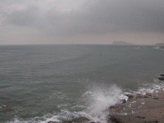 2018/4/18 江の島くすむ春雨の朝、北風に抑えられたうねりの合間にサーファー達がぷかりぷかり